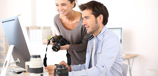 Fotograf und Fotografin sitzen vor einem PC